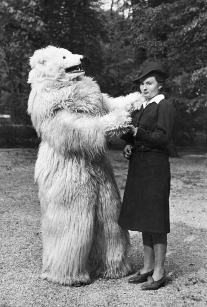 Unhappy woman dances with person in a polar bear costume.  German, ca. 1935